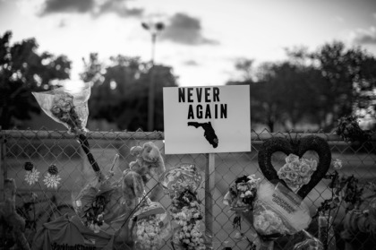 A Never Again sign hangs at a memorial for Marjory Stoneman Douglas High School.