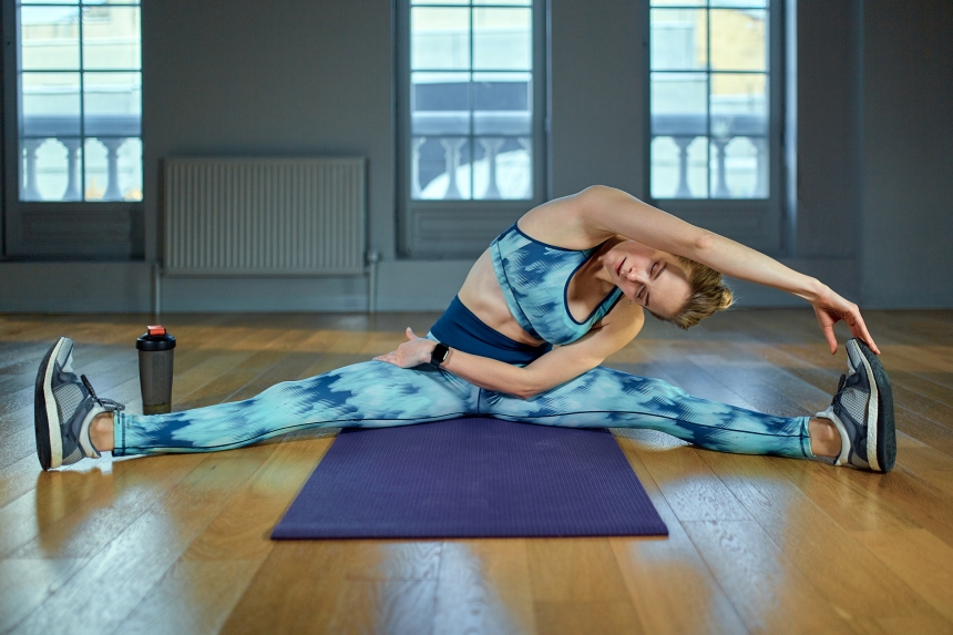 Staying flexible. Young beautiful woman in sportswear doing stretching while sitting on the floor in front of window at gym